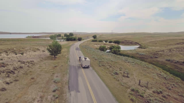 drone. establishing aerial view following a truck pulling a camper trailer down country road through badlands national park - badlands national park video stock e b–roll