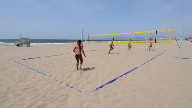 ws establishing master shot of female beach volleyball players, showing the whole court,  serving and playing. - newoutdoors stock videos & royalty-free footage