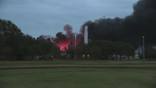 establishing shot from a school footbal field of a large fire at a texas refinery in port neches. - ゴールポスト点の映像素材/bロール