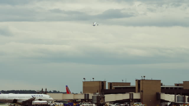establishing shot nondescript small town airport terminal; activity at gates, jet takes off overhead in the moody sky. - generic location stock videos & royalty-free footage
