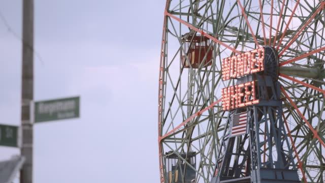 establishing shot of a ferris wheel in coney island, brooklyn at dusk - 4k - coney island stock videos and b-roll footage