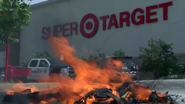 establishing shot of a fire burning in the parking lot of a super target in minneapolis, minnesota after rioting and looting following the death of... - looting stock videos & royalty-free footage