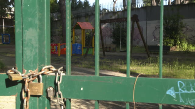 establishing shot of a locked playground during the coronavirus pandemic in rome italy - healthcare and medicine or illness or food and drink or fitness or exercise or wellbeing video stock e b–roll