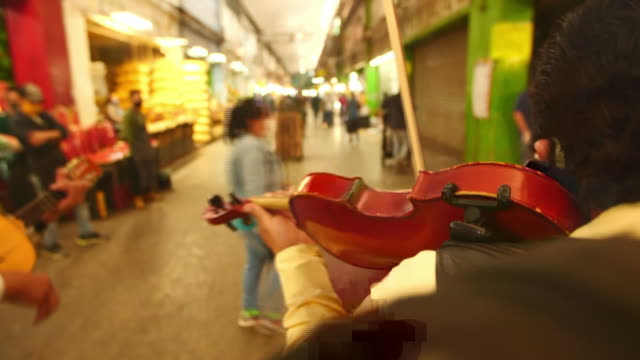 establishing shot of a man playing the violin at mexico city food market during the coronavirus pandemic. - healthcare and medicine or illness or food and drink or fitness or exercise or wellbeing stock videos & royalty-free footage