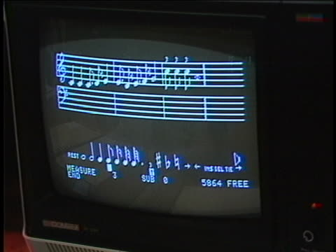 establishing shot of a man using paddle controllers to create a simple musical scale an apple ii computer. - computer stock videos & royalty-free footage