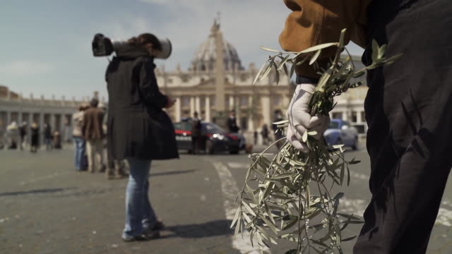 establishing shot of a man wearing a rubber glove holding an olive branch in st peter's square on palm sunday during the covid19 pandemic in italy - healthcare and medicine or illness or food and drink or fitness or exercise or wellbeing video stock e b–roll
