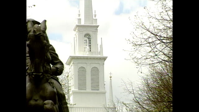 establishing shot of a new hampshire town with a church and steeple in the background and a statue in the foreground. - steeple stock videos & royalty-free footage