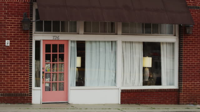 vídeos y material grabado en eventos de stock de establishing shot of a quaint small town storefront business on main street; possibly a lamp or furniture store. - cerrado