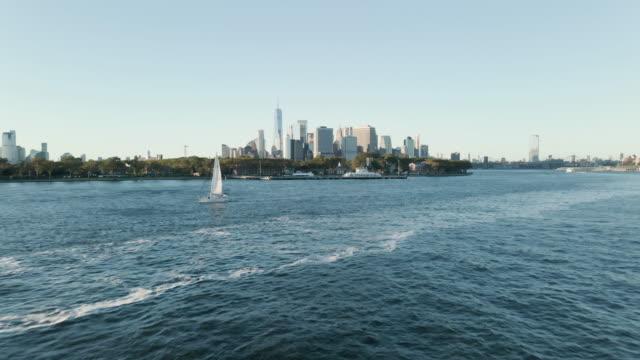 vídeos y material grabado en eventos de stock de establishing shot of a sailboat passing new york city - puerto de nueva york