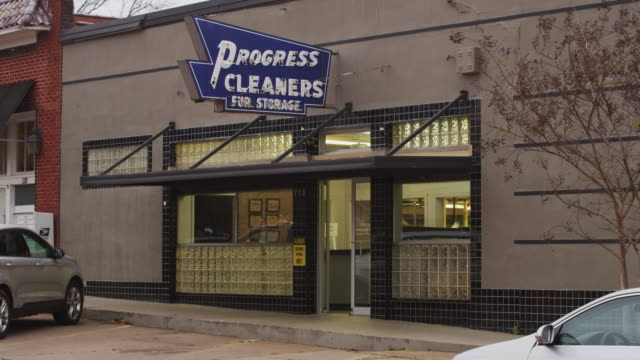 """vídeos de stock e filmes b-roll de establishing shot of a small dry cleaning storefront with cars parked in the street and a vintage neon sign which reads """"progressive cleaners fur storage."""" - establishing shot"""