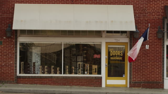 "Establishing shot of a small town store front business called ""Bill's Doors & Hardware"" featuring a brick exterior, awning and Texas flag waving in the breeze."