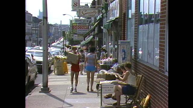 vidéos et rushes de establishing shot of a street with shops and people walking in philadelphia. - philadelphie
