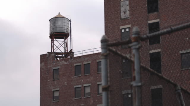 Establishing shot of a water tower in top of a New York City apartment building.