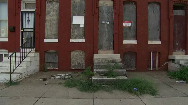 establishing shot of an abandoned row house with boarded up windows in baltimore; maryland. - vacancyサイン点の映像素材/bロール