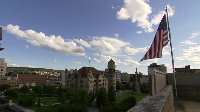establishing shot of an american flag and the lackawanna county courthouse in scranton pennsylvania - crime or recreational drug or prison or legal trial stock-videos und b-roll-filmmaterial