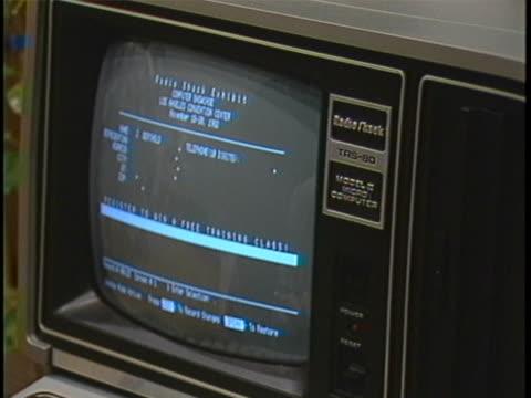 establishing shot of an elderly woman using a radioshack trs-80 microcomputer at a trade show. - viraggio monocromo video stock e b–roll