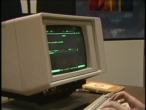 establishing shot of an older woman typing on a sperry univac computer with a green monochrome monitor at a trade show. close up shot of her hands... - viraggio monocromo video stock e b–roll