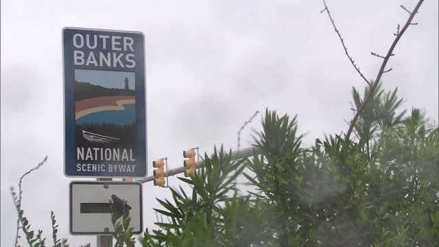 establishing shot of an outer banks national scenic byway sign during hurricane dorian in nags head, north carolina. - 2010 2019 stock videos & royalty-free footage