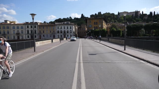 establishing shot of bicyclists on a bridge over the arno river in florence italy during the coronavirus pandemic - healthcare and medicine or illness or food and drink or fitness or exercise or wellbeing video stock e b–roll