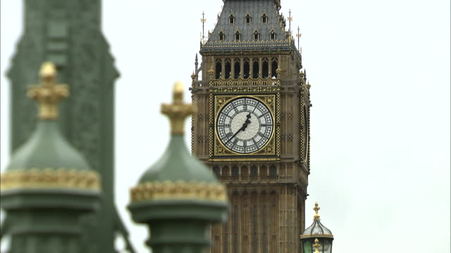 establishing shot of big ben and the british parliament building in london england with traffic passing by. - music or celebrities or fashion or film industry or film premiere or youth culture or novelty item or vacations stock videos & royalty-free footage