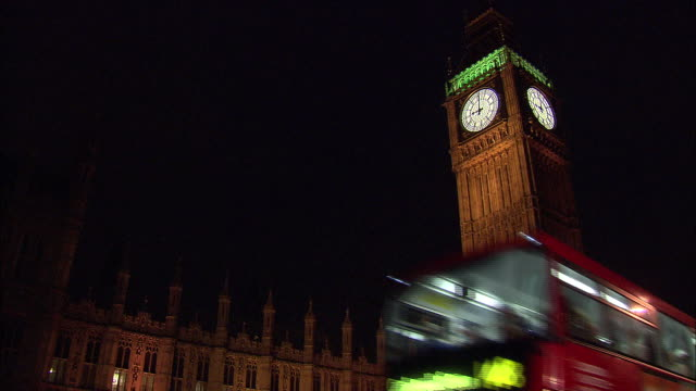 establishing shot of big ben at night with a double decker bus crossing in front. - music or celebrities or fashion or film industry or film premiere or youth culture or novelty item or vacations stock videos & royalty-free footage
