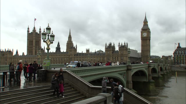 establishing shot of big ben, the british parliament and westminster bridge, including pedestrians crossing and walking down a stairway. - music or celebrities or fashion or film industry or film premiere or youth culture or novelty item or vacations stock videos & royalty-free footage