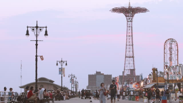 establishing shot of brooklyn's coney island boardwalk at dusk - 4k - coney island stock-videos und b-roll-filmmaterial