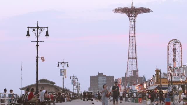 establishing shot of brooklyn's coney island boardwalk at dusk - 4k - coney island stock videos and b-roll footage