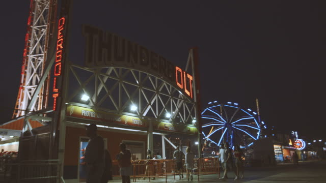 establishing shot of brooklyn's coney island boardwalk at night - 4k - coney island stock-videos und b-roll-filmmaterial