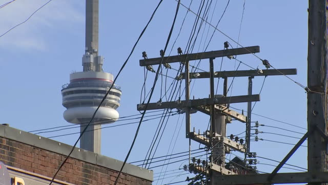establishing shot of cn tower behind powerlines in kensington market. - music or celebrities or fashion or film industry or film premiere or youth culture or novelty item or vacations stock videos & royalty-free footage