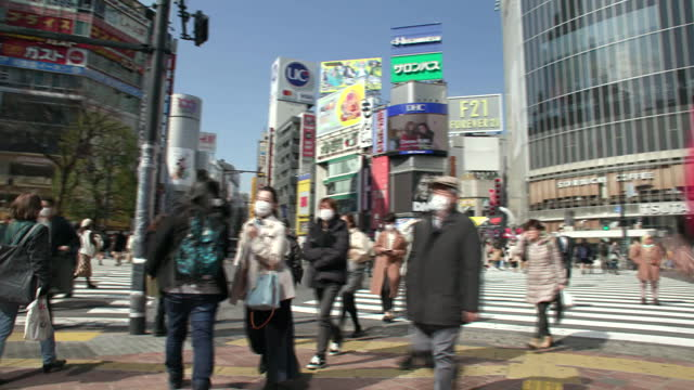 establishing shot of crowds of people, some wearing surgical face masks, at a busy intersection in tokyo, japan. - healthcare and medicine or illness or food and drink or fitness or exercise or wellbeing点の映像素材/bロール
