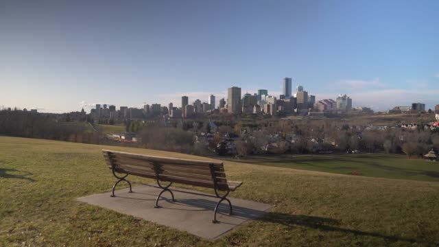 establishing shot of edmonton skyline with a bench in the foreground - alberta stock videos & royalty-free footage