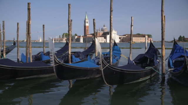 establishing shot of empty gondolas on the grand canal in venice italy during the coronavirus pandemic - healthcare and medicine or illness or food and drink or fitness or exercise or wellbeing video stock e b–roll