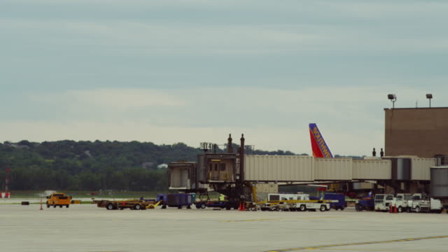 establishing shot of empty passenger loading ramp at nondescript, small airport terminal station; - generic location stock videos & royalty-free footage