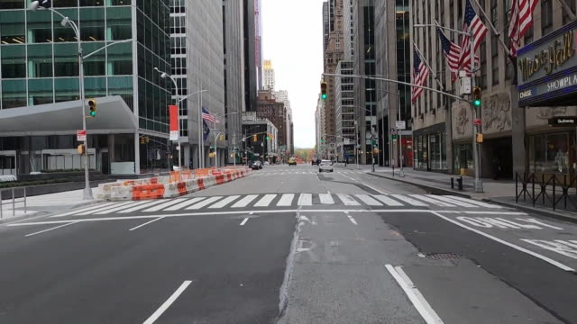 establishing shot of empty streets at the intersection of 49th street and sixth avenue in new york city driving by radio city music hall and entrance... - radio city music hall stock videos & royalty-free footage