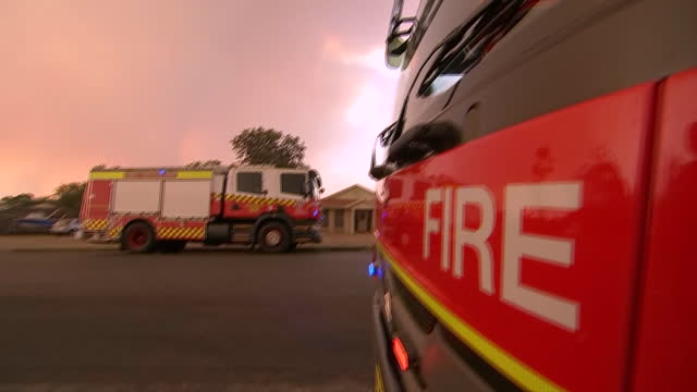 establishing shot of fire trucks near homes on a residential street in australia. - environment or natural disaster or climate change or earthquake or hurricane or extreme weather or oil spill or volcano or tornado or flooding stock videos & royalty-free footage