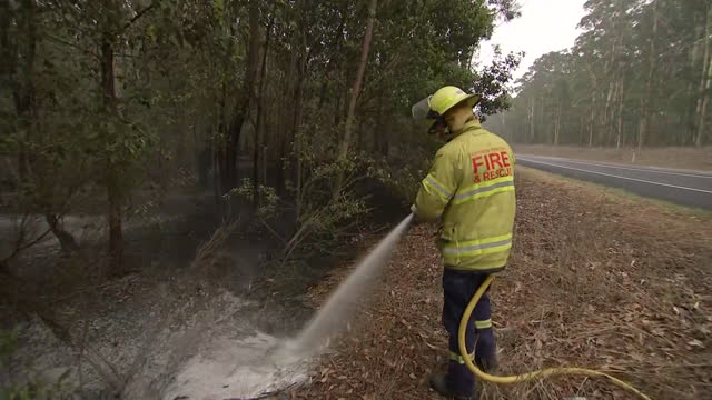 establishing shot of firefighters spraying fire retardant on vegetation in australia. - environment or natural disaster or climate change or earthquake or hurricane or extreme weather or oil spill or volcano or tornado or flooding stock videos & royalty-free footage