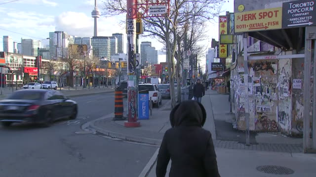 establishing shot of kensington market sign on street corner with toronto skyline and cn tower in the background. - music or celebrities or fashion or film industry or film premiere or youth culture or novelty item or vacations stock videos & royalty-free footage
