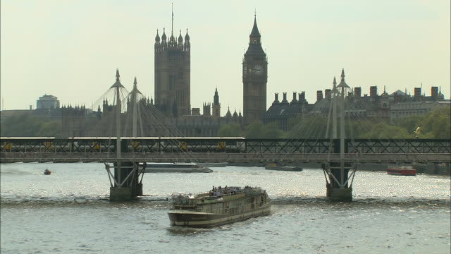 establishing shot of london with big ben and parliament in the background. boat traffic crosses the thames river. - music or celebrities or fashion or film industry or film premiere or youth culture or novelty item or vacations stock videos & royalty-free footage