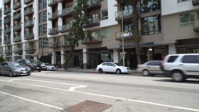 establishing shot of luxury condos on grand and 10th in in busy downtown los angeles the cars are traveling south - stockwerk stock-videos und b-roll-filmmaterial