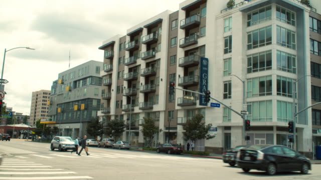 establishing shot of luxury condos on grand and 10th in in busy downtown los angeles the cars are traveling south - city of los angeles stock videos & royalty-free footage