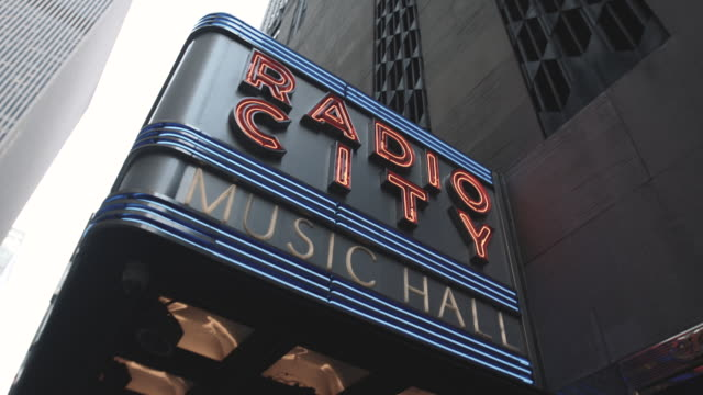 establishing shot of new york city's radio city hall marquee - marquee nightclub manhattan stock-videos und b-roll-filmmaterial
