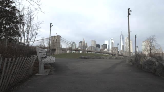vídeos y material grabado en eventos de stock de establishing shot of new york city's skyline on a cloudy day - puente de brooklyn