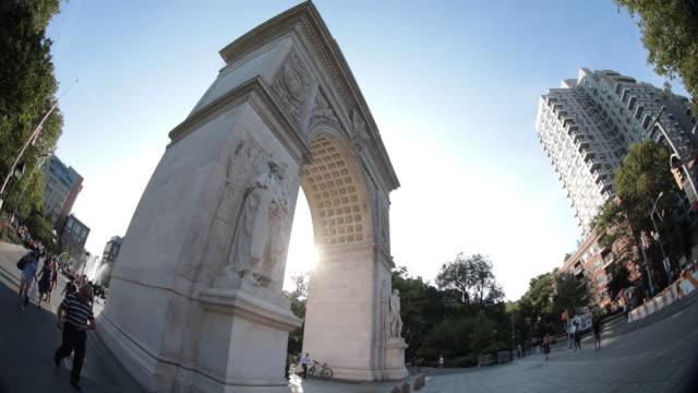establishing shot of new york city's washington square park on a sunny afternoon - 門点の映像素材/bロール