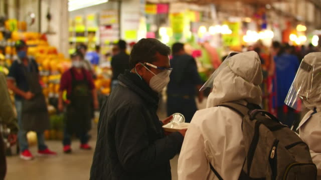 establishing shot of person in full ppe taking a man's temperatur as he walks through mexico city food market during the coronavirus pandemic. - healthcare and medicine or illness or food and drink or fitness or exercise or wellbeing stock videos & royalty-free footage