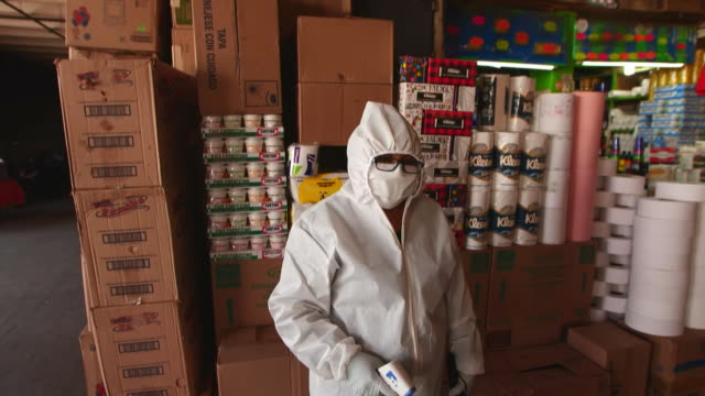 establishing shot of person in full ppe taking someone's temperature at mexico city food market during the coronavirus pandemic. - healthcare and medicine or illness or food and drink or fitness or exercise or wellbeing 個影片檔及 b 捲影像