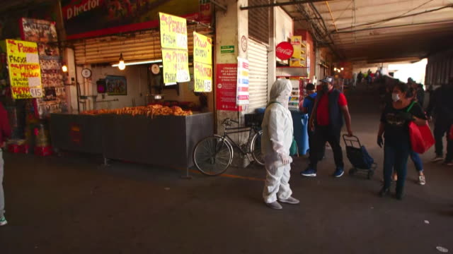 establishing shot of person in full ppe taking temperatures at mexico city food market during the coronavirus pandemic. - healthcare and medicine or illness or food and drink or fitness or exercise or wellbeing 個影片檔及 b 捲影像