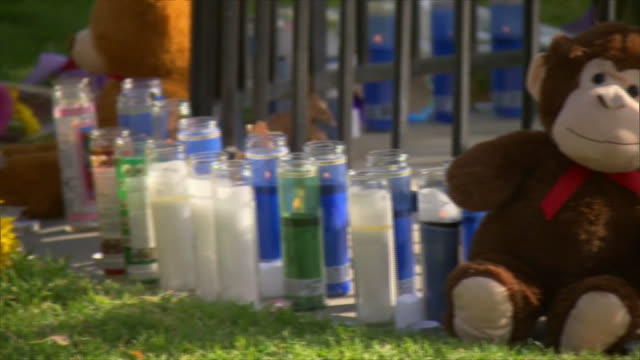 establishing shot of prayer candles and flowers left at a makeshift memorial in central park after the saugus high school mass shooting in santa... - santa clarita stock videos & royalty-free footage