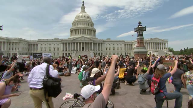 vidéos et rushes de establishing shot of protesters kneeling outside the u.s. capitol building during a rally in washington d.c. following the death of george floyd. - poing levé