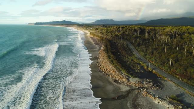 establishing shot of road next to beach. - new zealand stock videos & royalty-free footage
